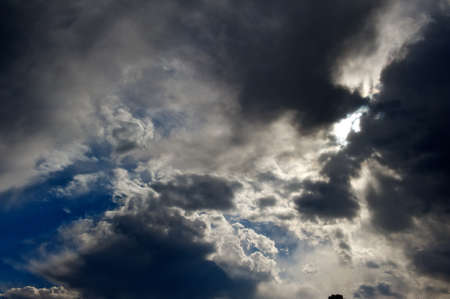 Angry sky with sun peeking through the clouds.  Stock Photo