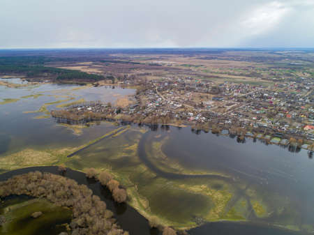 Flying over the river in the spring flood. Flooding of fields of villages.