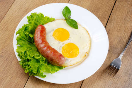 Fried eggs with sausages, lettuce and basil