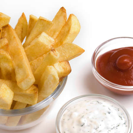 Fried potato chips in the glass bowl with dipping sauces aside over white background