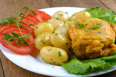 Fried fish with new potatoes, tomatoes, lettuce and herbs in the white plate photo