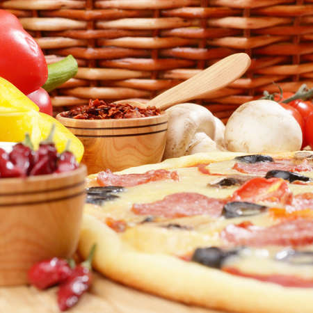 Pepperoni pizza with cherry and mushrooms on the kitchen table photo
