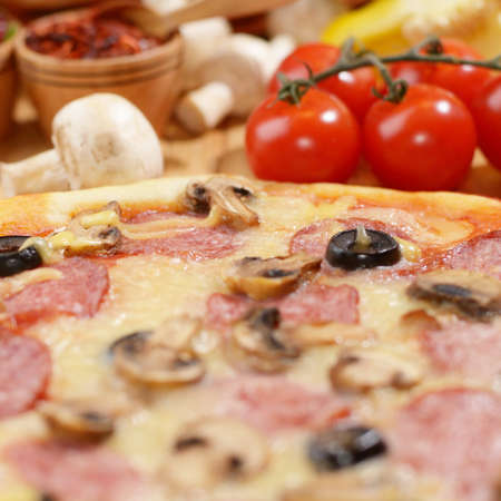 Pepperoni pizza with cherry and mushrooms on the bamboo kitchen table photo