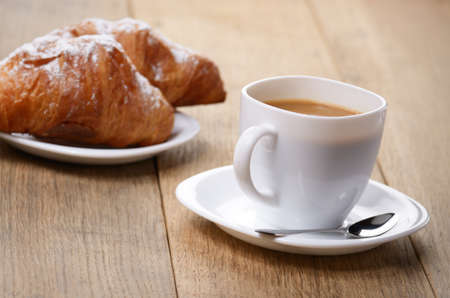 Morning cappuccino coffee with croissants on the wooden table
