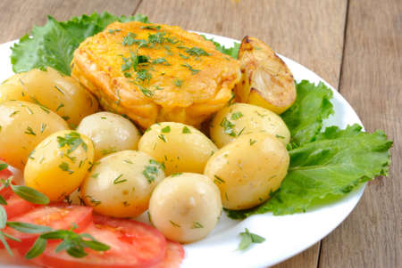 Fried fish with boiled new potatoes, lettuce and tomatoes in the white plate photo