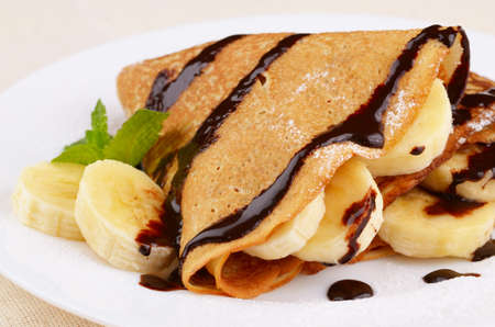 French style crepes with banana, chocolate sauce and sugar powder Stock Photo