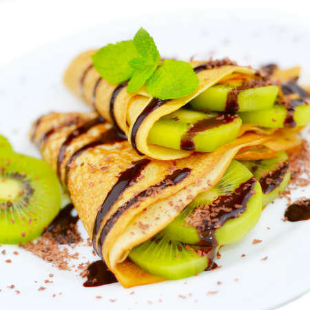 hotcakes: French style kiwi crepes with chocolate sauce and chips isolated on white Stock Photo