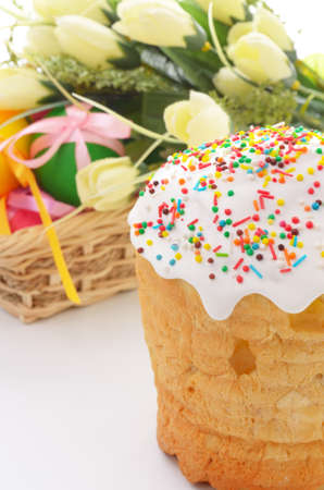 Easter cake and basket of painted eggs over floral background photo