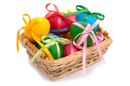 Easter eggs with bows in the basket over white background photo