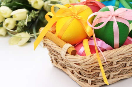 Easter eggs with bows in the basket with flowers at background
