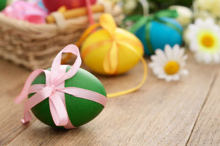 april flowers: Easter eggs with bows in the basket over floral background