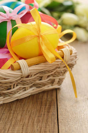Easter eggs with bows in the basket over floral background