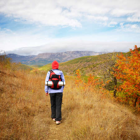 Female hiker with backpack walking in mountain area Stock Photo