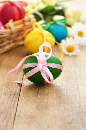 Easter eggs with bows in the basket over floral background Stock Photo - 12455363