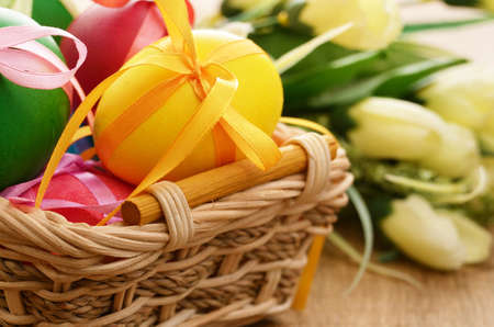 easter basket: Easter eggs with bows in the basket over floral background