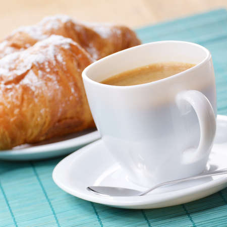 Morning cappuccino coffee with croissant on the wooden table photo