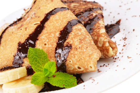 Crepes with banana and chocolate syrup over white photo