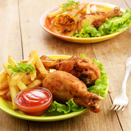 Fried drumsticks with french fries on the table Stock Photo