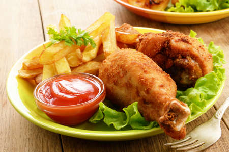 fried chicken: Fried drumsticks with french fries on the table Stock Photo
