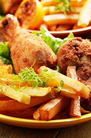 Fried drumsticks with french fries on the table photo