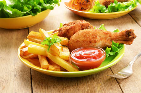 Fried chicken legs with french fries on the table Stock Photo