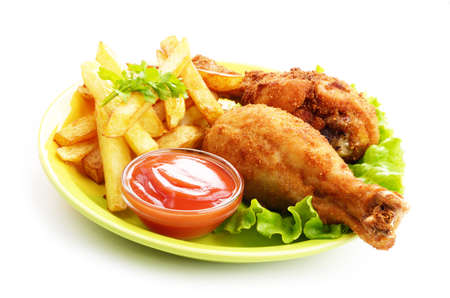 Fried chicken legs with french fries and ketchup over white