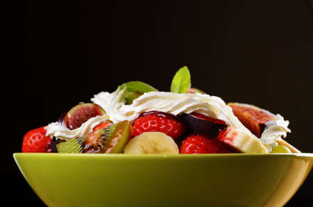 Healthy fruit mix salad over dark background photo