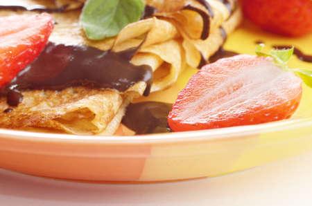chocolate syrup: Crepes de fresa con jarabe de chocolate y menta closeup foto