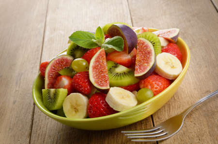Healthy fruit mix salad on the kitchen table photo