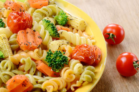 Pasta fusilli salad with broccoli, carrot, corn, and tomatoes on the kitchen table