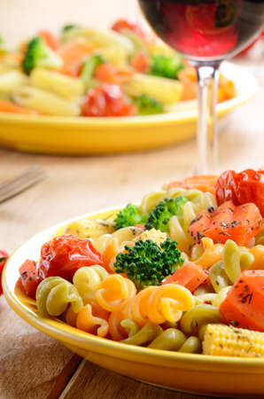 Pasta fusilli with broccoli, carrot, corn, and tomatoes on the kitchen table photo