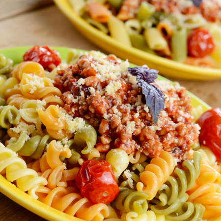 Pasta fusilli with bolognese tomato beef sauce and dried tomatoes on the kitchen table photo