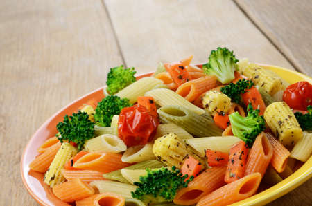 Pasta penne salad with broccoli, carrot, corn, and tomatoes on the wooden table photo