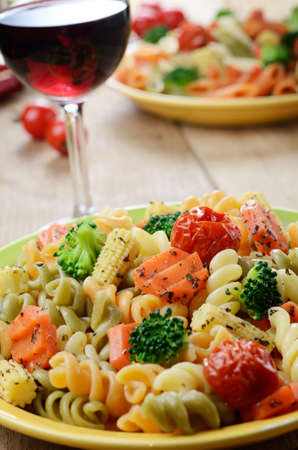 Pasta fusilli salad with broccoli, carrot, corn, dried tomatoes on the kitchen table Stock Photo