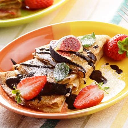chocolate syrup: Crepes de fresa con jarabe de chocolate, higos y menta sobre la mesa Foto de archivo