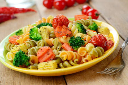 Pasta fusilli salad with broccoli, carrot, corn and tomatoes on the kitchen table