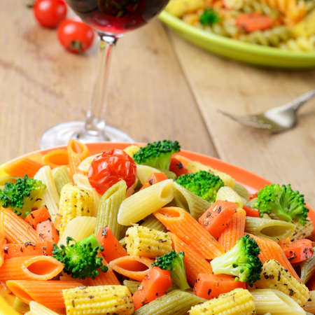 Pasta penne salad with broccoli, carrot, corn served with red wine photo