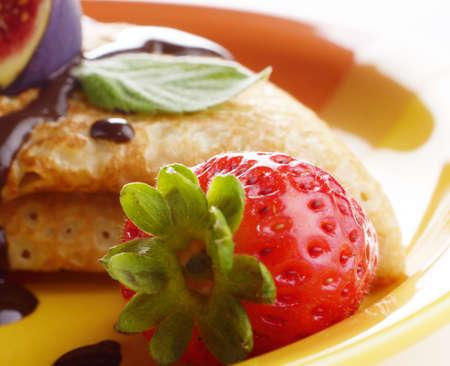 chocolate syrup: Crepes de fresa con jarabe de chocolate, higos y menta closeup foto Foto de archivo