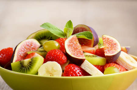 Healthy mixed fruit salad on the kitchen table photo