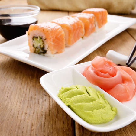 sushi plate: Philadelphia roll sushi on a white plate with soy sauce wasabi and ginger Stock Photo