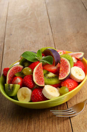 Healthy fruit mix salad on the kitchen table with copy-space photo