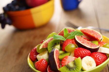 Healthy mixed fruit salad on the kitchen table with copy-space photo