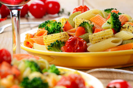 Pasta penne salad with broccoli, carrot, corn, served with red wine photo