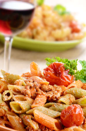 Pasta penne with bolognese sauce served with red wine photo