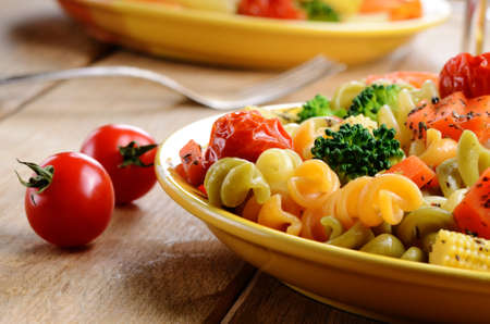 Pasta fusilli salad with broccoli, carrot, corn, and tomatoes on the kitchen table photo