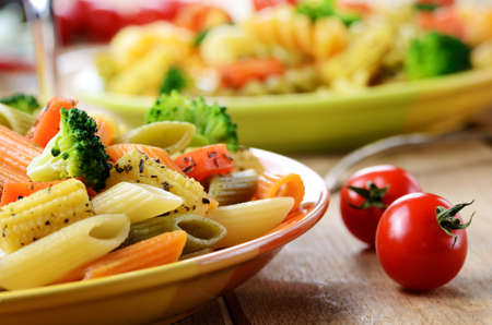 Pasta penne salad with broccoli carrot corn and tomatoes on the kitchen table photo