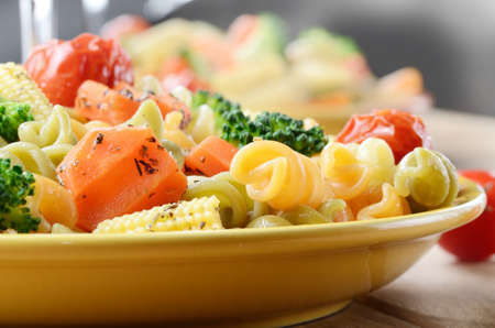 Pasta fusilli salad with broccoli carrot corn tomatoes photo