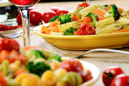 Pasta salad with broccoli, carrot, corn, served with red wine photo
