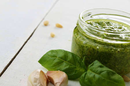 Glass jar of pesto sauce on white kitchen table with copy-space photo