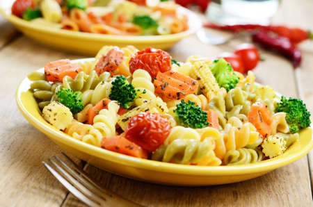 Pasta fusilli salad with broccoli carrot corn and tomatoes on the kitchen table Stock Photo